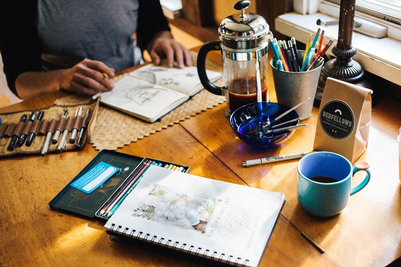 An artist drawing and drinking coffee.